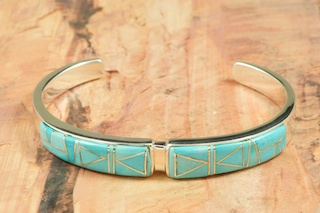 Beautiful Bracelet featuring Genuine Sleeping Beauty Turquoise inlaid between ribbons of Sterling Silver. Precision channel inlay. Heavy Gauge Sterling Silver Bracelet  Designed by Navajo Artist Calvin Begay. Signed by the artist. 